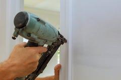 Clavito del carpintero usando el arma del clavo a los moldeados en puertas, Fotografía de archivo