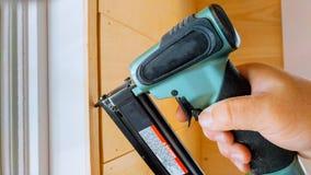 Clavito del carpintero usando el arma del clavo a los moldeados que enmarcan el ajuste, con la etiqueta de advertencia herramient Fotos de archivo libres de regalías