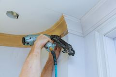 Clavito del carpintero usando el arma del clavo para coronar el ajuste que enmarca que moldea, con la etiqueta de advertencia her Imagenes de archivo