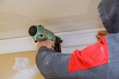 Clavito del carpintero usando el arma del clavo para coronar el ajuste que moldea, etiqueta de advertencia herramientas eléctrica Fotografía de archivo