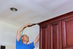 Clavito del carpintero usando el arma del clavo para coronar moldear en los armarios de cocina que enmarcan el ajuste Imagen de archivo