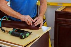 Clavito del carpintero usando el arma del clavo para coronar moldear en los armarios de cocina que enmarcan el ajuste Imagen de archivo libre de regalías