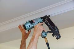 Clavito del carpintero usando el arma del clavo para coronar el ajuste que enmarca que moldea, Fotos de archivo