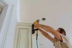 Clavito del carpintero usando el arma del clavo para coronar moldear en los armarios de cocina que enmarcan el ajuste, Imagenes de archivo
