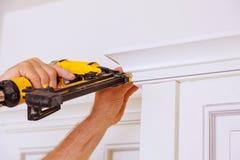 Clavito del carpintero usando el arma del clavo para coronar moldear en los armarios de cocina que enmarcan el ajuste, Fotografía de archivo libre de regalías