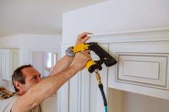 Clavito del carpintero usando el arma del clavo para coronar moldear en los armarios de cocina que enmarcan el ajuste, Foto de archivo libre de regalías