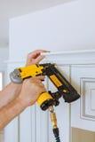 Clavito del carpintero usando el arma del clavo para coronar moldear en los armarios de cocina que enmarcan el ajuste, Fotos de archivo