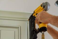 Clavito del carpintero usando el arma del clavo para coronar moldear en los armarios de cocina que enmarcan el ajuste, Fotografía de archivo