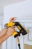 Clavito del carpintero usando el arma del clavo para coronar moldear en los armarios de cocina que enmarcan el ajuste, Imagen de archivo