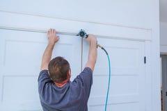 Clavito usando el arma del clavo a los moldeados en puertas, ajuste que enmarca del carpintero, con la etiqueta de advertencia he Foto de archivo libre de regalías