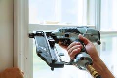 Clavito usando el arma del clavo a los moldeados en ventanas, ajuste que enmarca del carpintero, Fotos de archivo