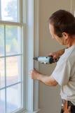 Clavito usando el arma del clavo a los moldeados en ventanas, ajuste que enmarca del carpintero, Fotografía de archivo