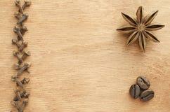 Clavos, anís de estrella, granos de café en una tabla de madera fotografía de archivo