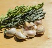 Clavos del ajo con la menta secada y del apio de monte en fondo de madera Foto de archivo libre de regalías