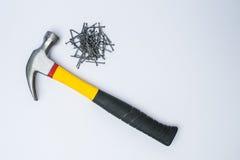 Clavos del martillo y del metal en un fondo blanco Fotos de archivo