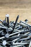 Clavos del metal en la tabla de madera Foto de archivo libre de regalías