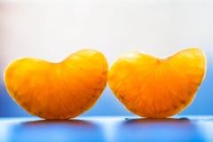 Clavos dulces maduros de la mandarina Segmento anaranjado dos en fondo azul foto de archivo libre de regalías