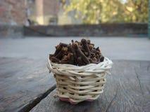 Clavos en la cesta de bambú en el tablero de madera Imagen de archivo libre de regalías