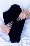 Clavos falsos coloridos largos hermosos en un fondo blanco y una base negra, los clavos para la exposición Imagen de archivo libre de regalías