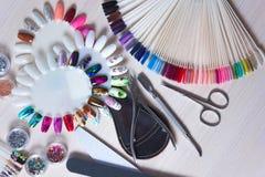 Clavos maravillosamente manicured en la mesa con las herramientas para la manicura Foto de archivo