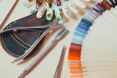 Clavos maravillosamente manicured en la mesa con las herramientas para la manicura Foto de archivo libre de regalías
