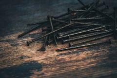 Clavos oxidados macros en el fondo de madera, entonado fotos de archivo