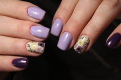 Clavos púrpuras del diseño de los colores de la manicura fotos de archivo libres de regalías
