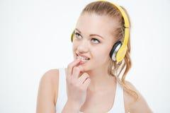 Clavos penetrantes de la mujer pensativa y el escuchar la música en auriculares Fotos de archivo libres de regalías