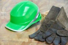 Clavos verdes del casco de seguridad y del guantelete en un fondo de madera Imagenes de archivo