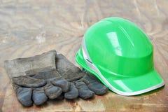 Clavos verdes del casco de seguridad y del guantelete en un fondo de madera Fotografía de archivo