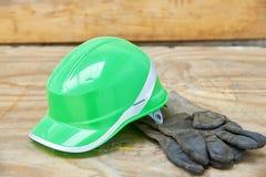 Clavos verdes del casco de seguridad y del guantelete en un fondo de madera Imagen de archivo