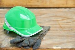 Clavos verdes del casco de seguridad y del guantelete en un fondo de madera Foto de archivo libre de regalías