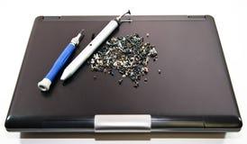 Clavos y destornillador en la cubierta de la computadora portátil Fotos de archivo libres de regalías