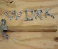Clavos y martillo en banco de trabajo foto de archivo