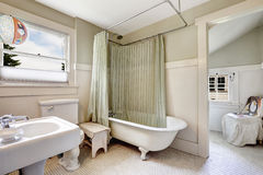 Claw foot tub with light green wraparound curtain. Stock Photos