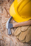 Claw hammer building helmet leather gloves on chipboard construc Stock Photo