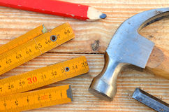 Claw hammer, carpenter meter, pencil and chisel. Claw hammer, carpenter meter, red pencil and chisel on wooden desk background Stock Image