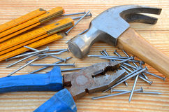 Claw hammer, carpenter meter, pliers and nails. On wooden desk background Stock Photography