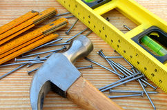 Claw hammer, carpenter meter, water-level and nails. On wooden desk background Stock Images