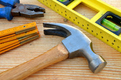 Claw hammer, carpenter meter, water-level and pliers. On wooden desk background Royalty Free Stock Photography