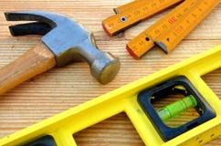 Claw hammer, carpenter meter, water-level. On wooden desk background stock photos