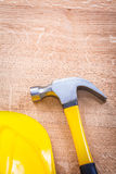 Claw hammer contruction helmet on wooden board Stock Photo