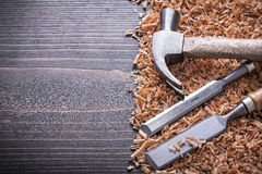 Claw hammer flat chisels and wooden shavings on Stock Photography