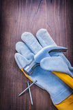 Claw hammer on glove and nails vintage wooden Royalty Free Stock Images