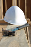 Claw Hammer and Hard Hat on Board Stock Photo