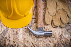 Claw hammer hard hat leather gloves on chipboard construction co Stock Photo