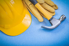 Claw hammer leather protective gloves building helmet on blue ba Royalty Free Stock Photo