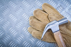 Claw hammer leather protective gloves on grooved metal plate con. Struction concept Royalty Free Stock Photography
