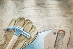 Claw hammer leather protective gloves stainless handsaw on wood Stock Images