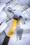 Claw hammer and nails with blueprints. Studio shot. claw hammer and nails with blueprints stock photos